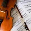 A violin and bow on sheet music — Stock Photo