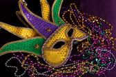Mardi gras mask and beads on a purple background — Stock Photo