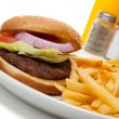 Hamburger and fries with ketchup and mustard, salt and pepper at a diner or cafe — Stock Photo #13421398