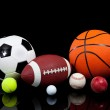 Assorted sports balls on a black background — Stock Photo #13422003