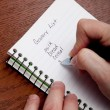 Hands writing a shopping list — Stock Photo