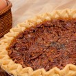 Pecan pie with ingredients on a wooden cutting board — Stock Photo