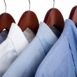 Blue dress shirts on wooden hangers — Stock Photo #13441061