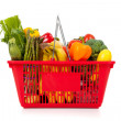 Red shopping basket with vegetables on white — Stock Photo #13441571