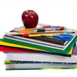 Stack of textbooks with school supplies on top — Stock Photo