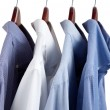 Blue dress shirts on wooden hangers — Stock Photo #13442388