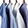 Blue dress shirts on wooden hangers - Foto de Stock