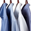 Blue dress shirts on wooden hangers - Stock Photo
