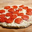 Frozen pepperoni pizza on a cutting board — Stockfoto