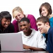 Multi-racial college students sitting around computer — Foto de stock #13446741