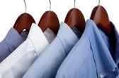 Blue dress shirts on wooden hangers — Stock Photo