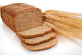 Loaf of wheat bread and shocks of wheat — Stock Photo