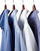 Blue dress shirts on wooden hangers — Stock Photo
