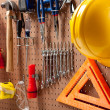 Peg board with tools and hard hat — Stock Photo
