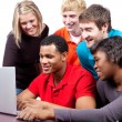 Multi-racial college students sitting around computer — Foto Stock #13452199