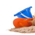 Beach scene with flipflops, sand, bucket and starfish — Stock Photo #13459458