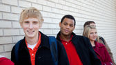 Multi-racial college students against a brick wall — Stock Photo