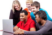 Multi-racial college students sitting around a computer — Stock Photo