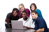 Collégiens multiraciale assis autour d'un ordinateur — Photo