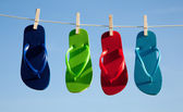 Row of flipflops against a blue sky — Stock Photo