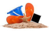 Beach scene with flipflops, sand, bucket and starfish — Stock Photo