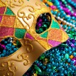 Gold mardi gras mask and beads — Stock Photo