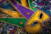 A yellow Mardi Gras mask and beads — Stock Photo