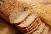 A loaf of bread with a shock of wheat on a wooden board — Stock Photo