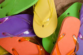 Vários flip-flops coloridos na areia — Fotografia Stock