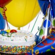 Birthday Cake, party hats and balloons - Stock Photo