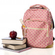 Stock Photo: Pink Patterned Back Pack with supplies and apple