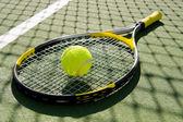 Raqueta de tenis y la bola en la cancha — Foto de Stock