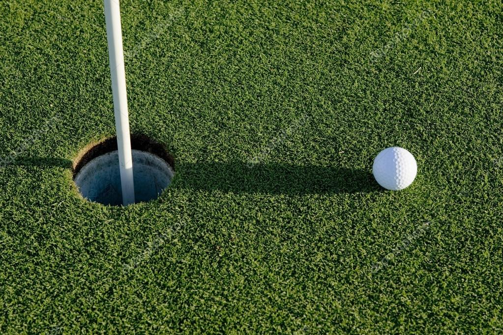 A white golf ball near the hole of a golfing green or course — Stock Photo #13643344