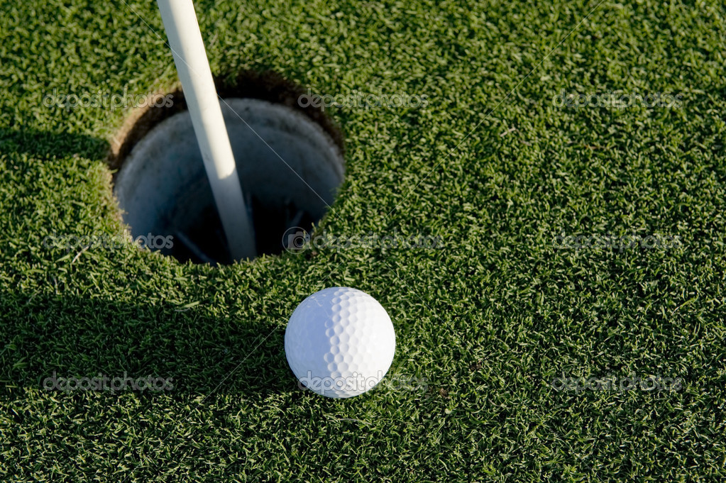 A white golf ball near the hole of a golfing green or course — Stock Photo #13643353