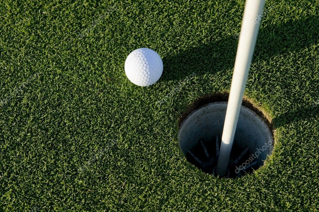 A white golf ball near the hole of a golfing green or course — Stock Photo #13643361
