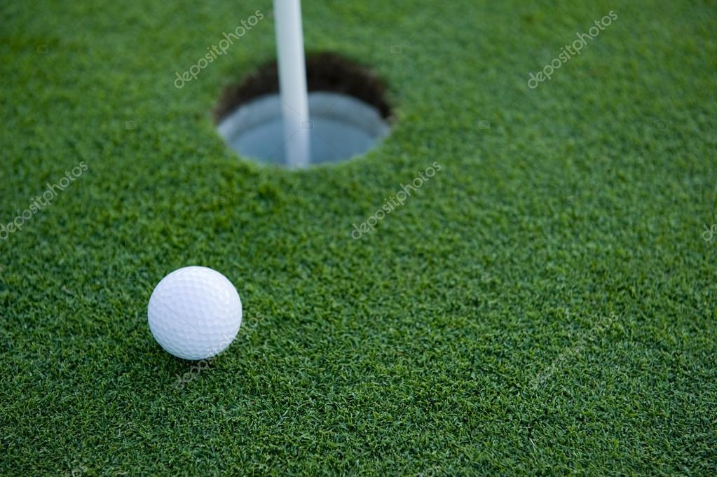 A white golf ball near the hole of a golfing green or course — Stock Photo #13643413