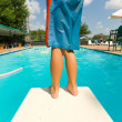 Young boy standing on the end of a diving board at a swimming pool — Stock Photo #13929567