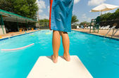 Young boy standing on the end of a diving board at a swimming pool — Stock Photo