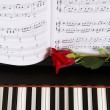 Sheet Music with Rose on piano — Stock Photo #13930351