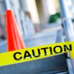 Caution tape with orange traffic cone — Stock Photo