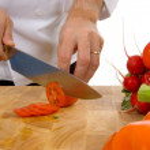 Professional chef slicing tomato — Stock Photo #13931952