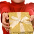 Young girl in red with gold Christmas present — Стоковая фотография