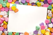 Blank note card surrounded, framed by candy hearts — Stock Photo