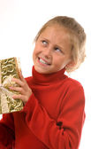 Young girl in red shaking gold Christmas present — Stock Photo