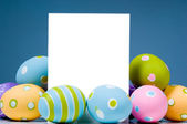 Brightly colored Easter Eggs surrounding white, blank notecard — Stock Photo