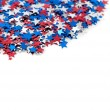 Red white and blue star shaped confetti on a white background — Stock Photo #13988199