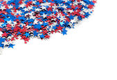 Red white and blue star shaped confetti on a white background — Stock Photo
