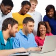 Diverse group of college students/friends looking at a computer — Stock Photo