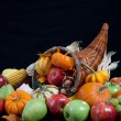 An overflowing cornucopia on a black background — Stock Photo