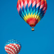 Two brightly colored hot air balloons with a sky blue background — Stock Photo